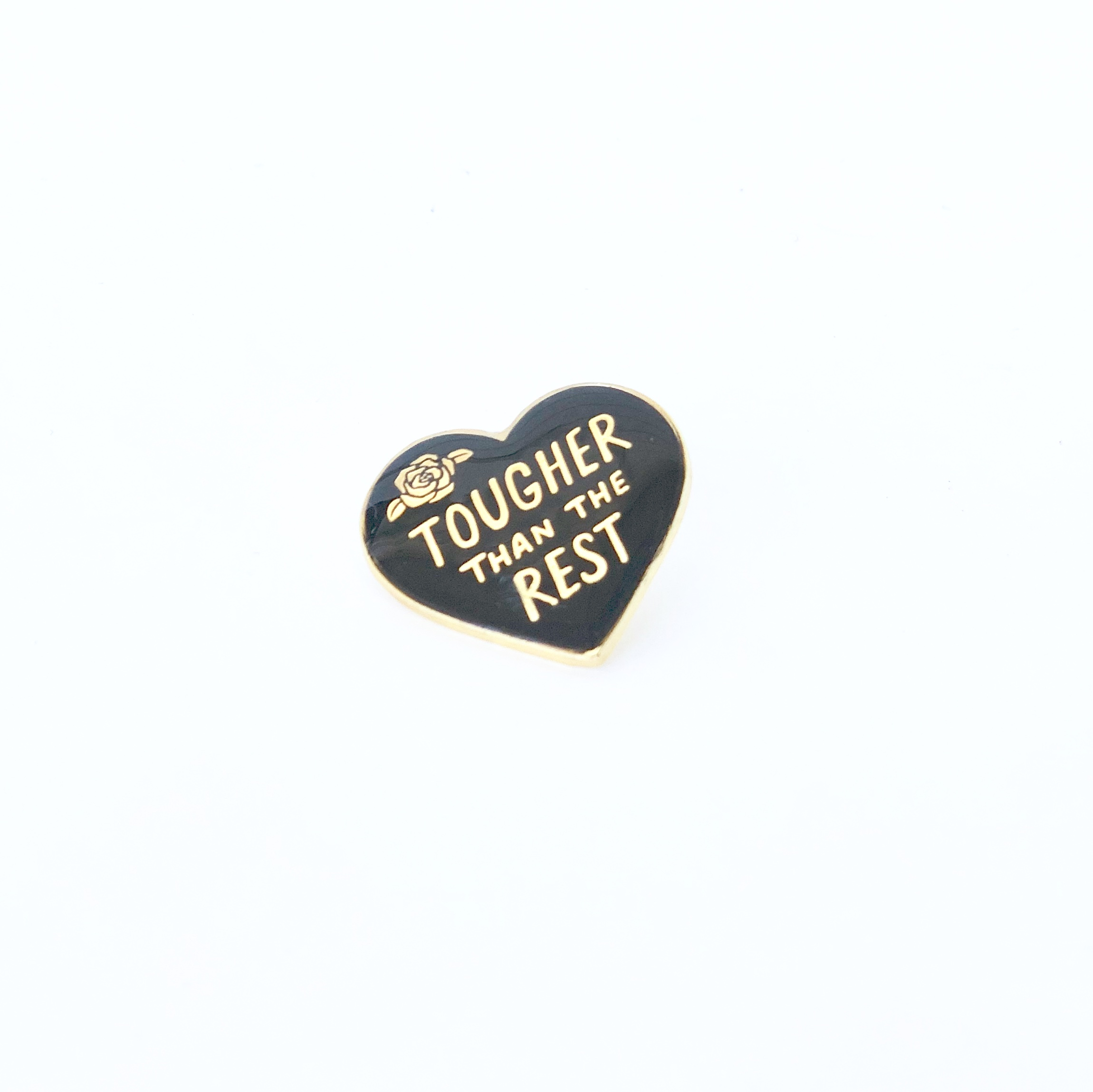 "Black enamel pin with the saying ""tougher than the rest."""