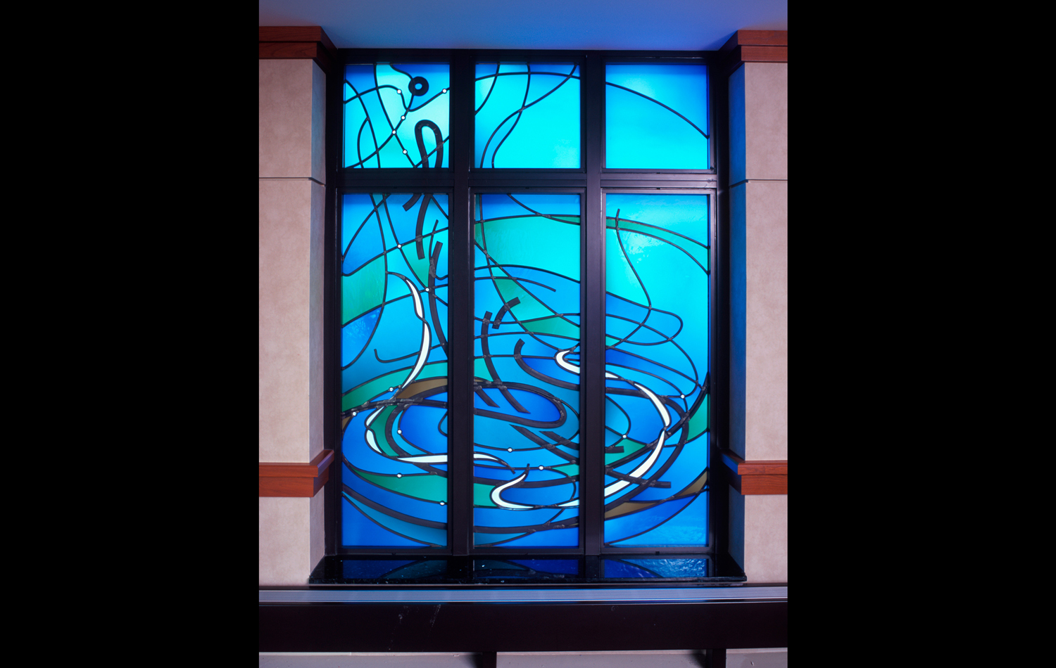 """""""Water"""" window: This window represents the concept of water, with all its connotations of abundance, cleansing, flood, and rebirth. As these ideas guided the rhythm and flow of the design, a single water drop emerged. It communicates that we may be one drop in the sea of life, but that God treasures us as a most precious individual, selectively nurturing us in our time of need."""