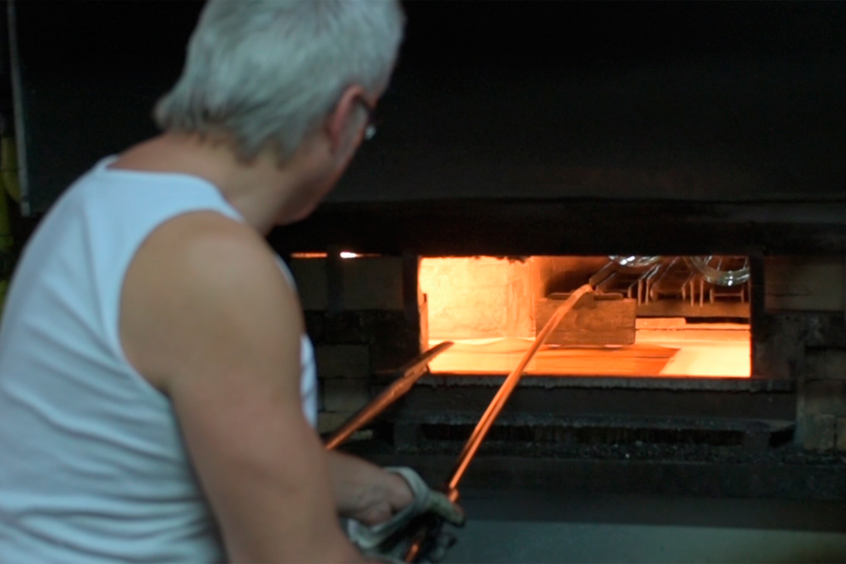 "Glass is re-heated and the sides fall flat.  A worker ""irons"" out any bumps."