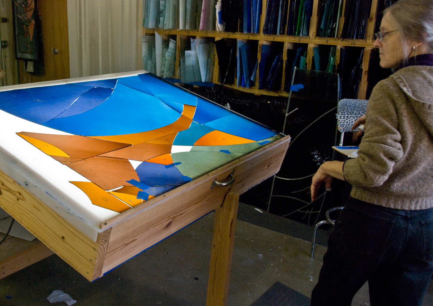 Cindy does a final color check before releasing a panel for fabrication.