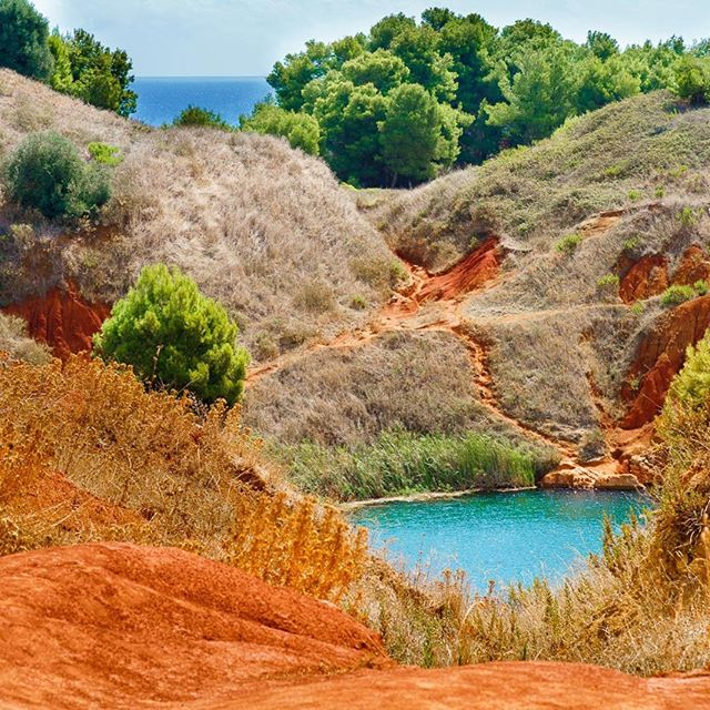 Bauxite Cave | Otranto The red of the land, the green of the lake, the yellow of the dry grass, the vivid green of the trees, the deep blue of the sea, the light blue of the sky...all in one picture. This is possible in #puglia.  #luxuryholiday #vacationinpuglia #salentotravel #weareinpuglia # #photographytours #experientialtourismpuglia #travelmore #goexplore #wonderfulplaces #lovetotravel #digitalnomads #rseekmoments #momentsofmine #postcardsfromtheworld #vacationgoals #travel #travelinspiration #ilovetotravel #beautifuldestinations #bestvacations #bestplacestogo #puglia365 #forbestravelguide #culturetrip