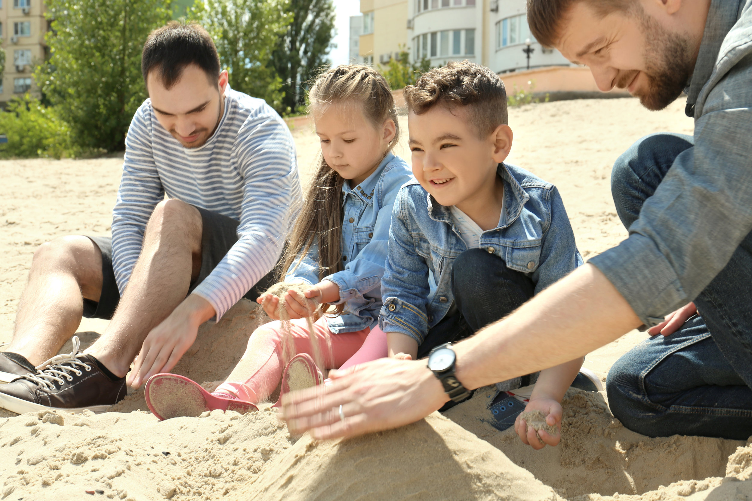 Men with children playing in sand.jpg