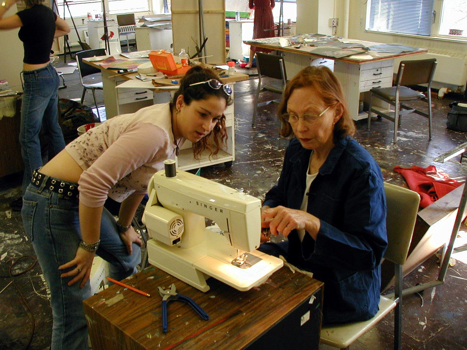 (right) Jackie Matisse instructing a student on how to use a sewing machine