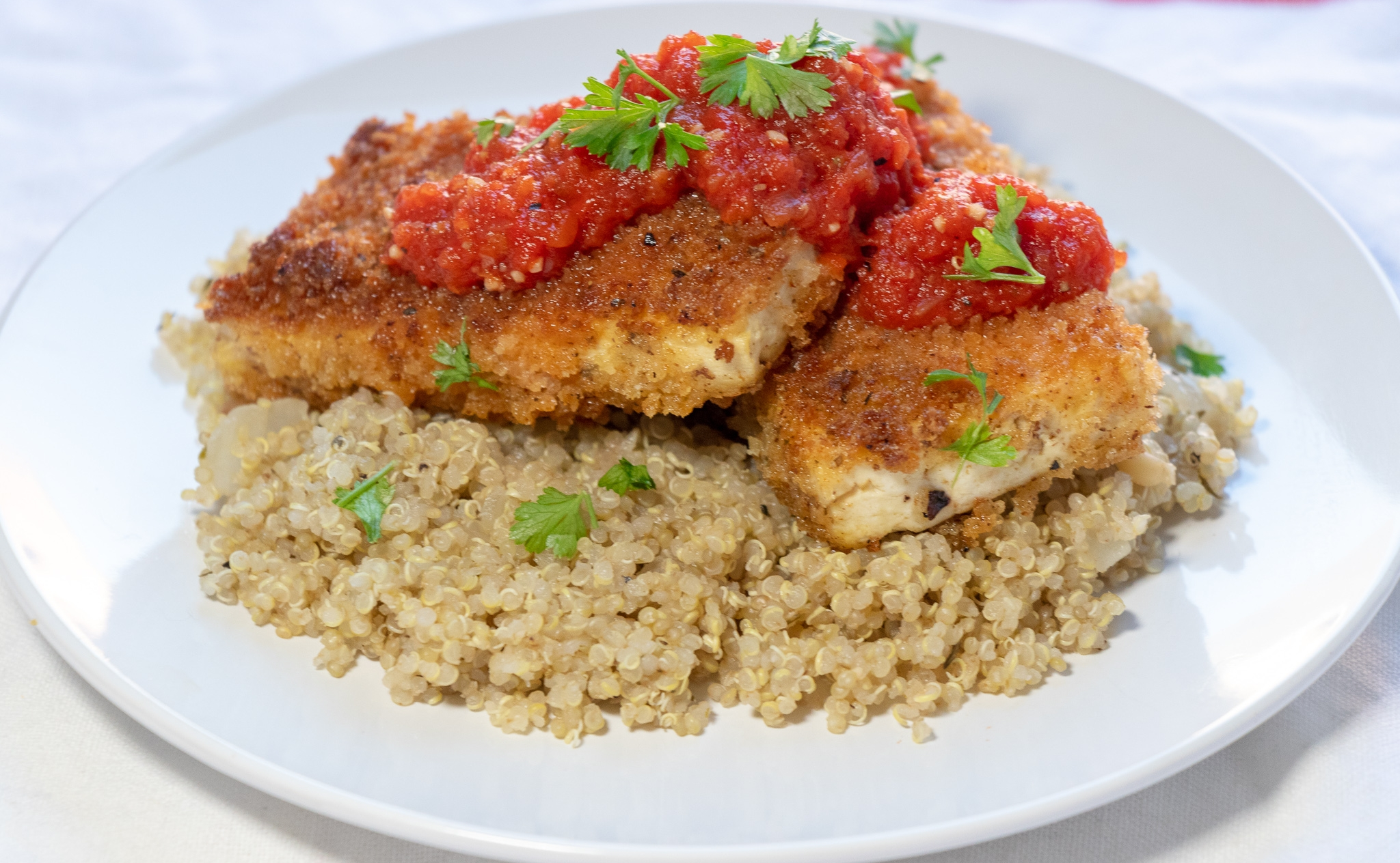 Crispy tofu on a bed of savory quinoa, covered in a delicious red pepper marinara makes for a quick and filling weeknight dinner. You can easily makes this recipe gluten free by using a gf flour blend, and gf panko. You could also use an air fryer to prepare the tofu if you have one, or try baking the tofu pieces if you prefer cooking without oil!