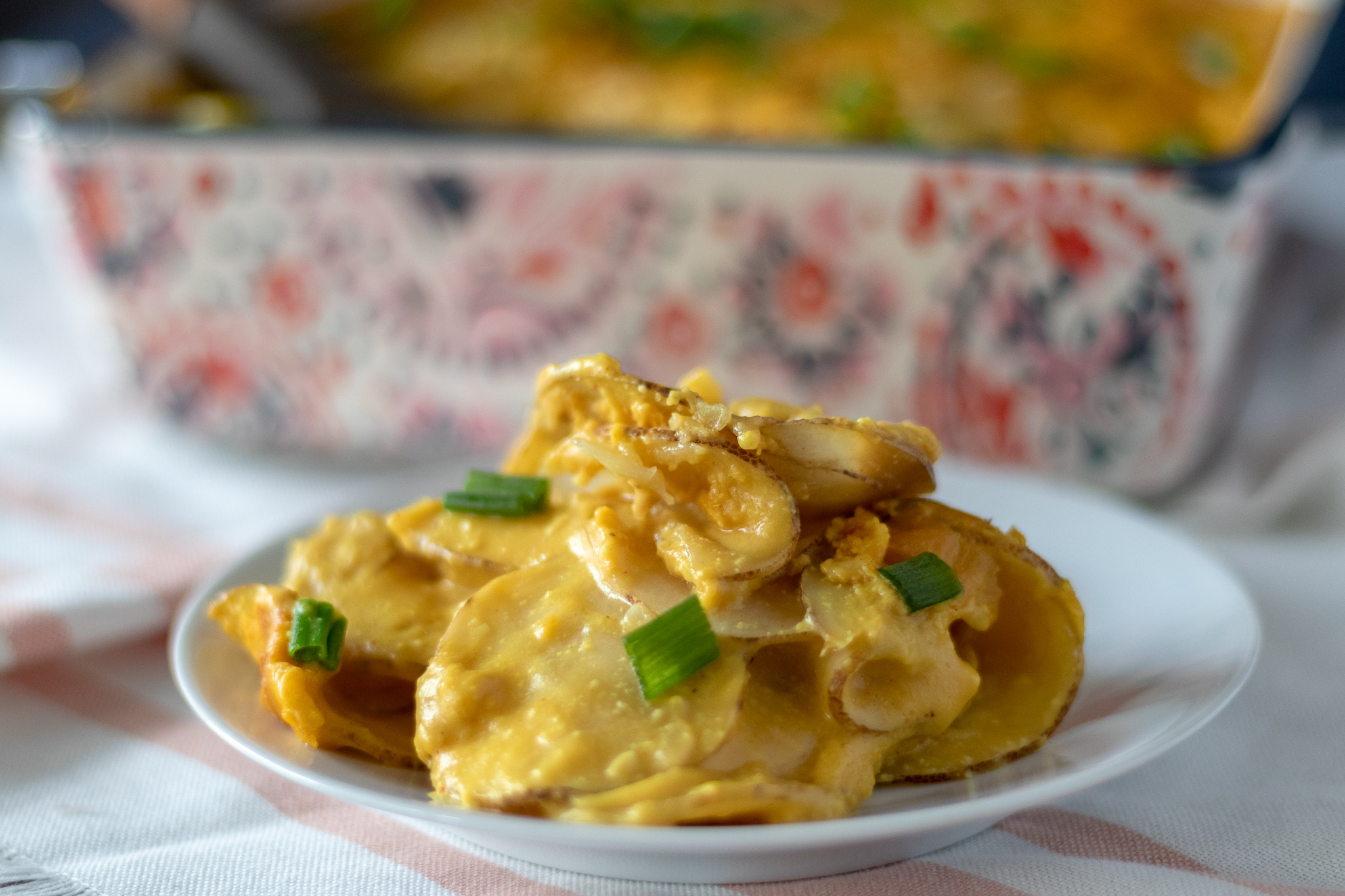 I love potatoes and I love cheese. So what's not to love about these super easy cheesy vegan scalloped potatoes. All you need is a pretty simple vegan cheese sauce, some thinly sliced potatoes, an 8x8 pan, and you are on your way to a veganized classic!