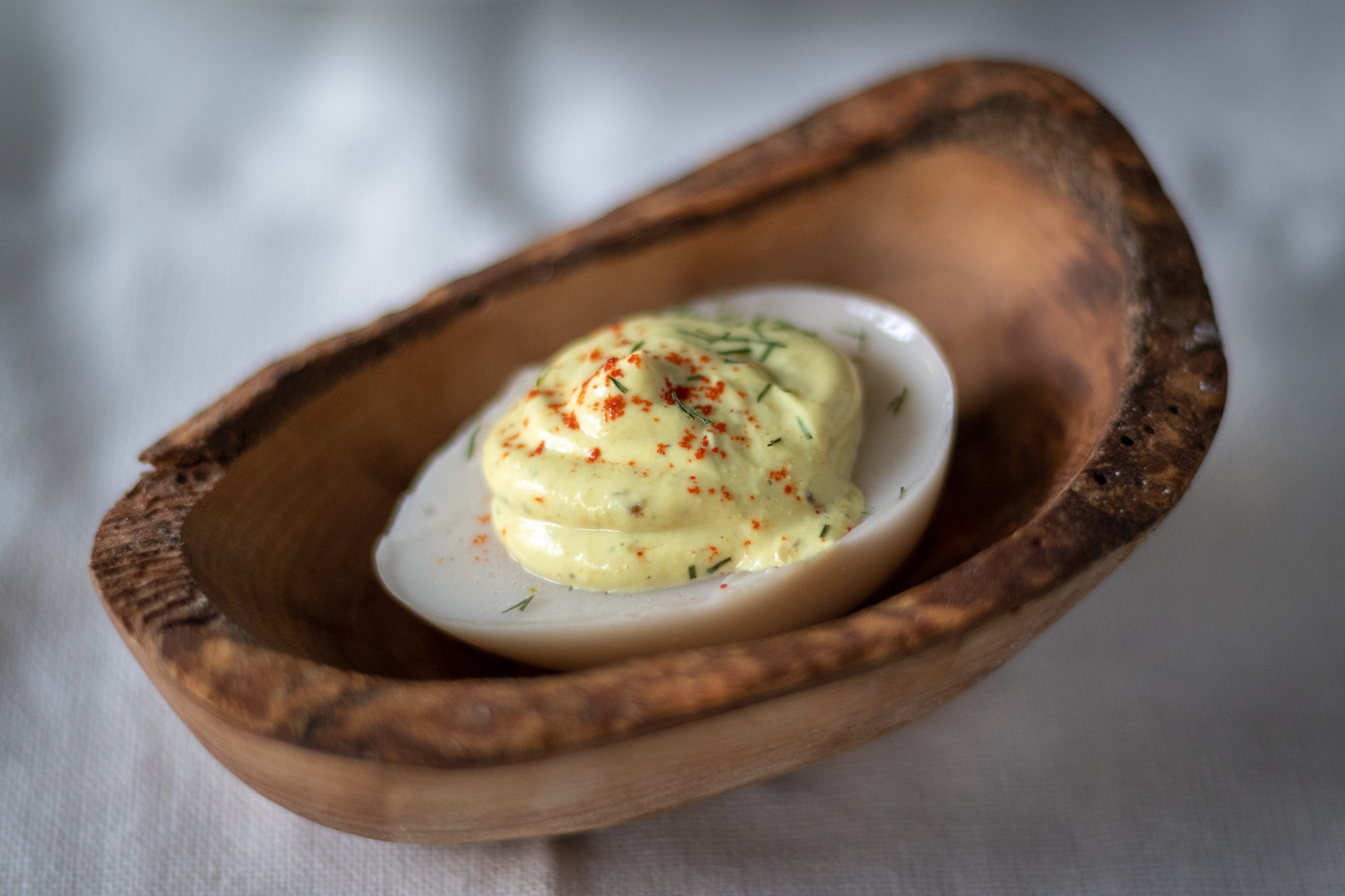 A single vegan deviled egg in a wooden serving dish