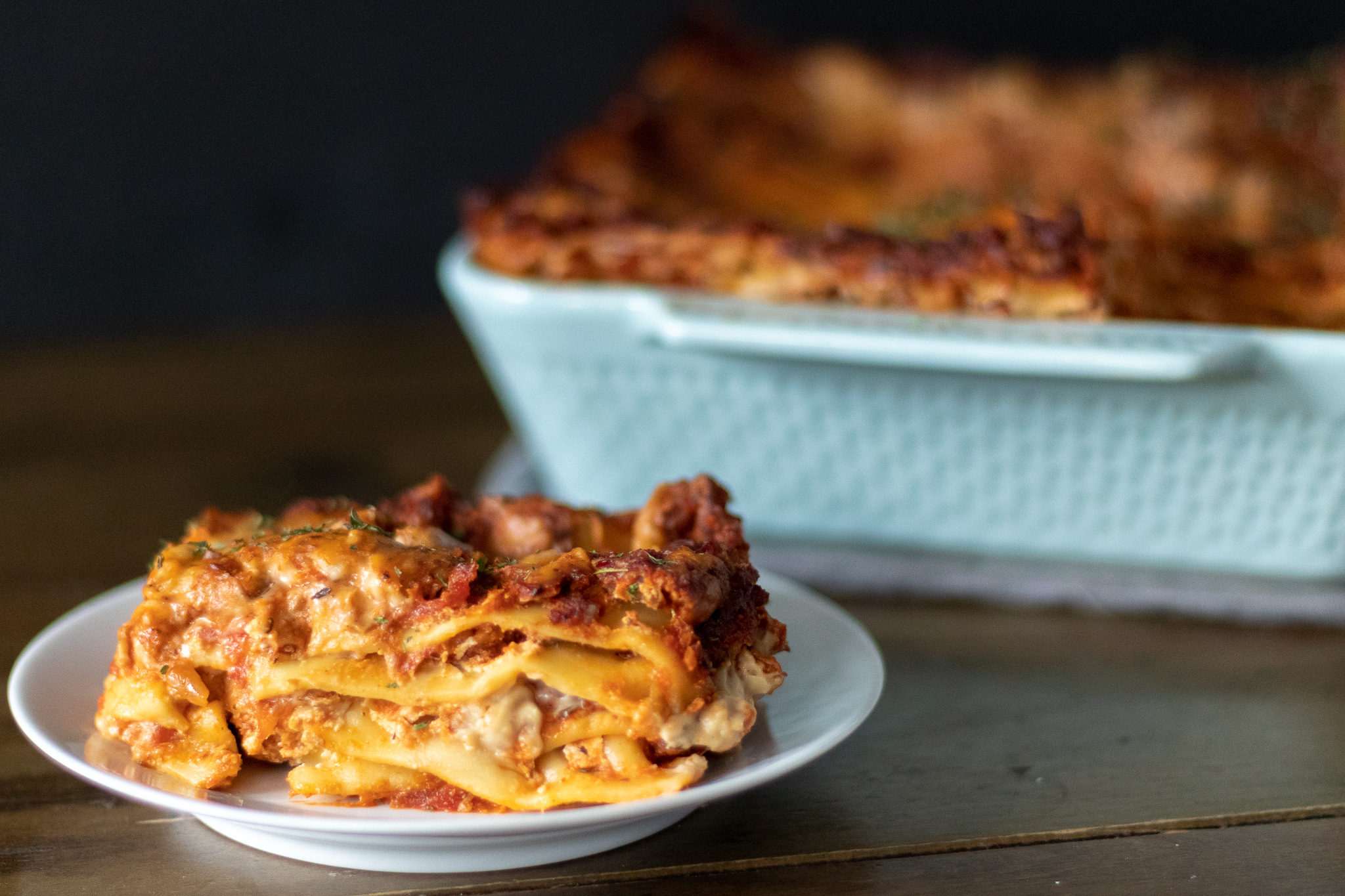 """If you have been looking for the perfect, cheesy, gooey, saucy, vegan lasagna, look no further! Layers of noodles, tofu ricotta, homemade marinara, and the perfect vegan mozzarella sauce make this lasagna the best vegan lasagna I have had, hands down! It's my go to dish to bake up for all of our non vegan friends and family, because no one ever even knows its vegan! We are house divided where lasagna is concerned, some preferring veggie lasagna, and others a classic """"meaty"""" lasagna. So I have given instruction on making this lasagna 2 ways! Because two kinds of lasagna are always better than one!! Right?!?!? If you are looking for a mini version that is perfect for meal prep, check out the links below for our  Muffin cup lasagna , and our  Lasagna stuffed peppers !!"""
