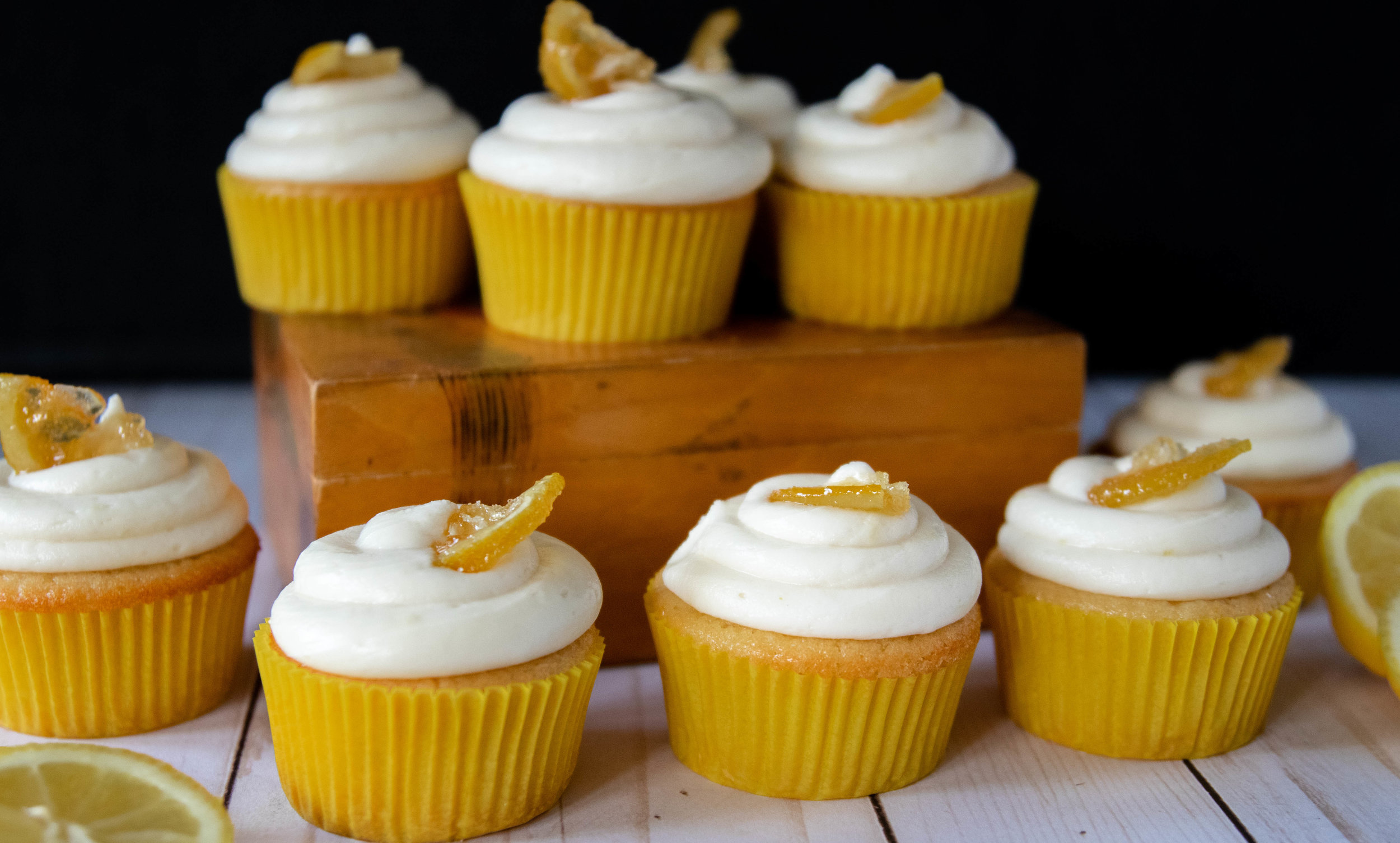 A closeup of delicious vegan lemon cupcakes with cream cheese frosting garnished with candied lemons.