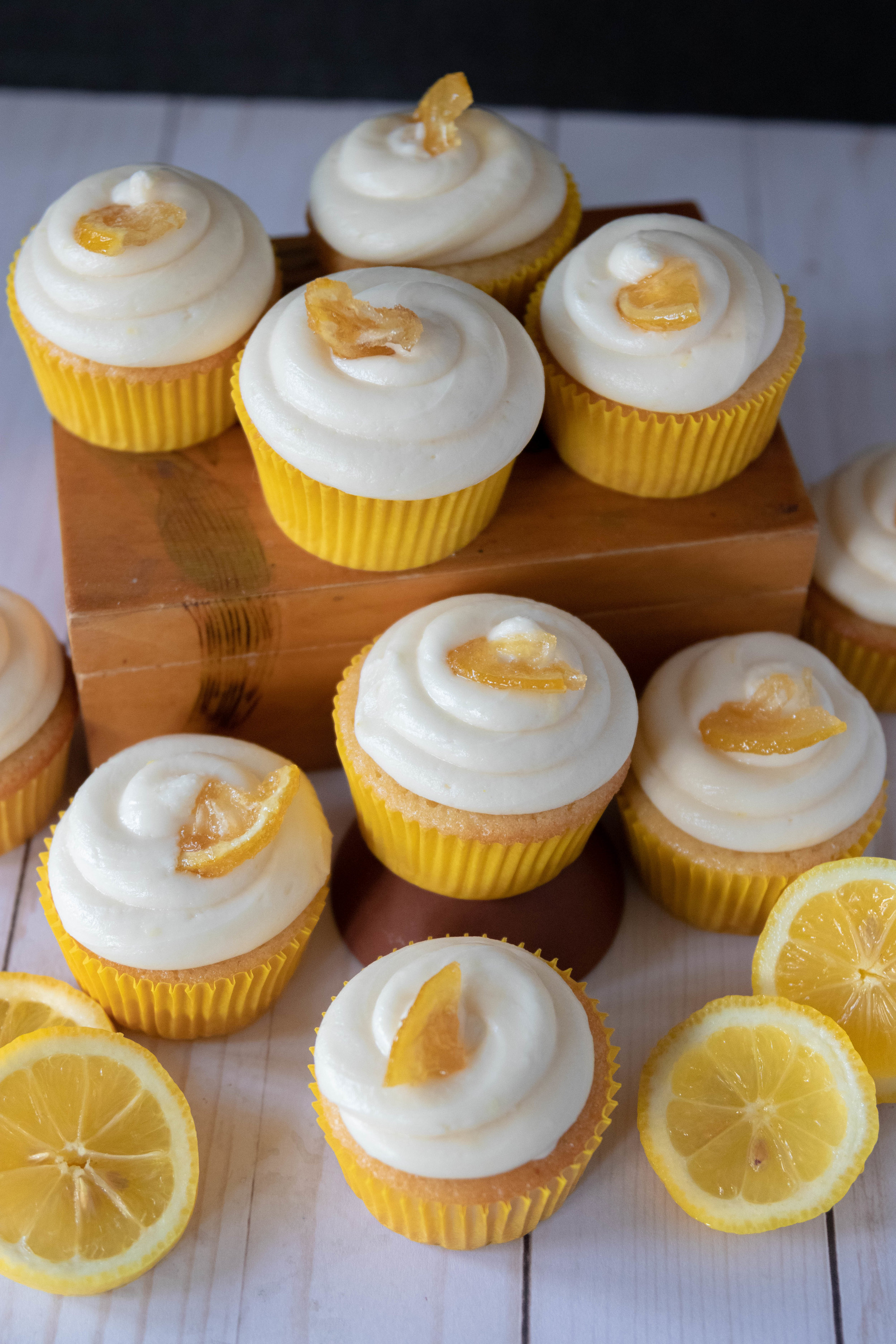 A spread of delicious vegan lemon cupcakes with cream cheese frosting garnished with candied lemons.
