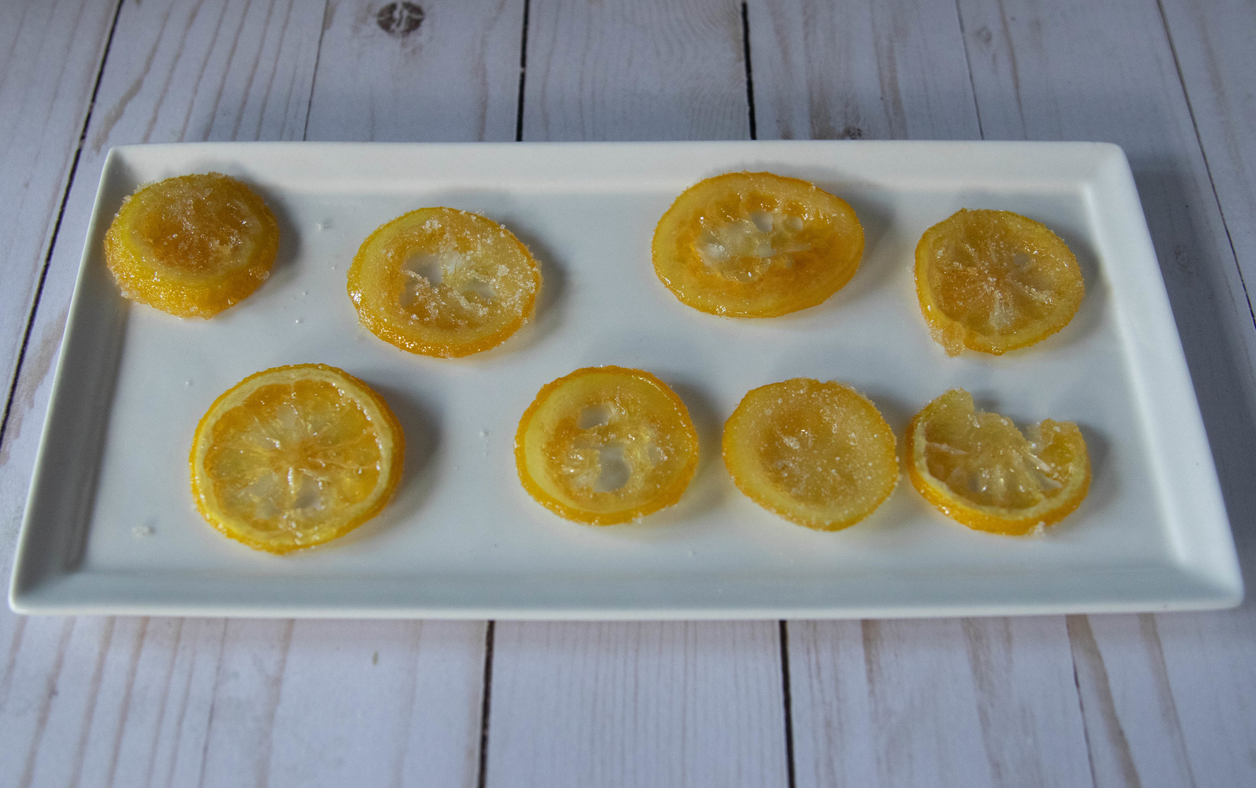 Plate of candied lemons with granulated sugar.