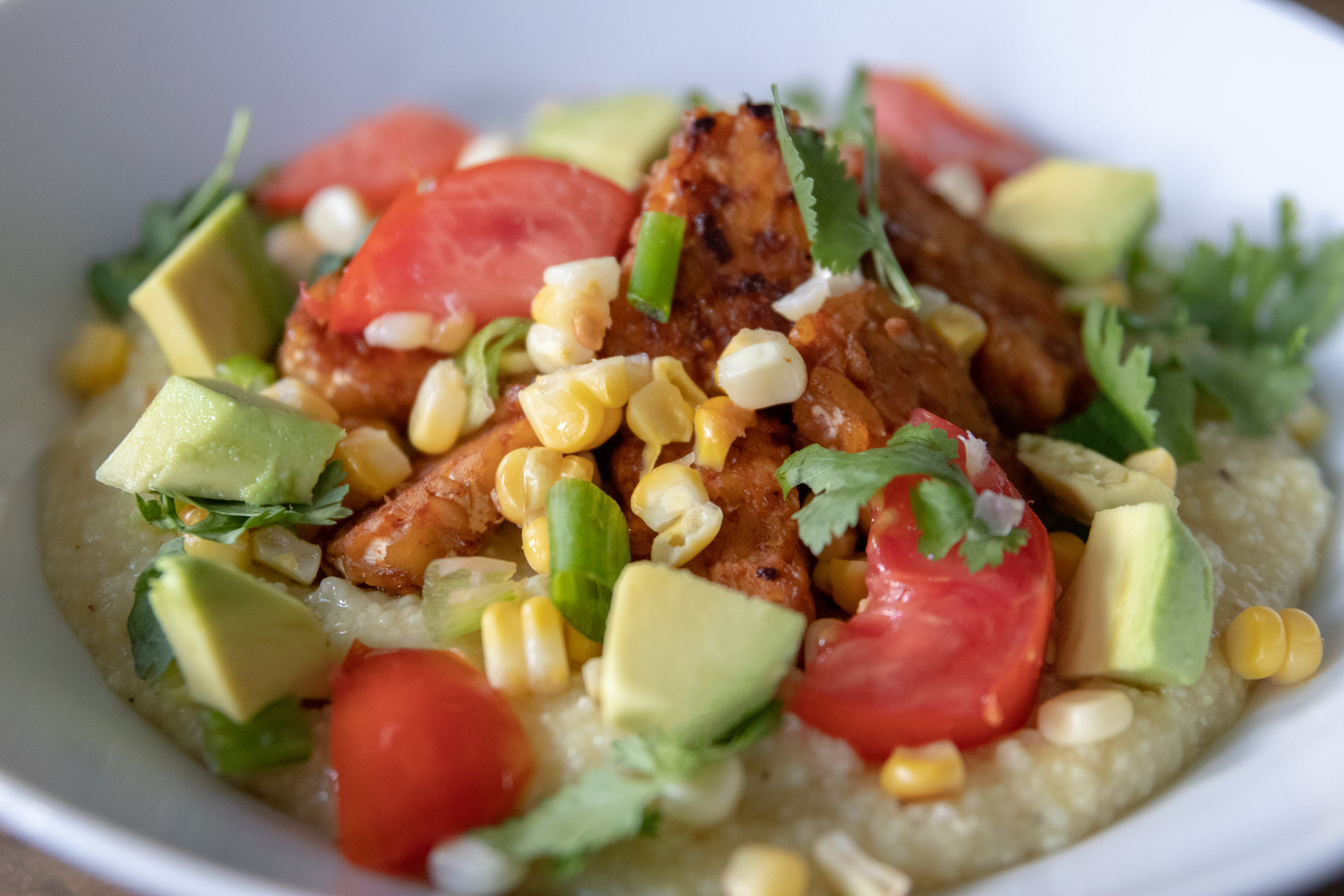 A bowl of grits topped with tempeh, corn, tomatoes, and scallions.
