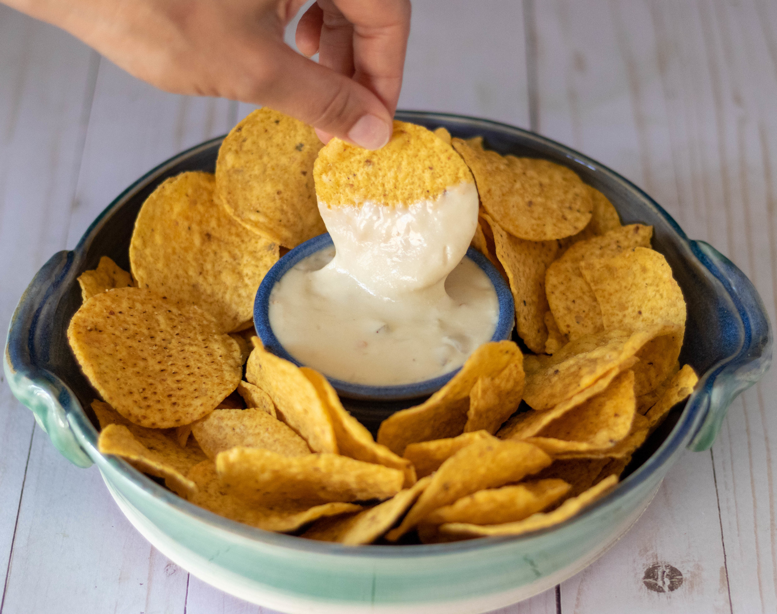 Dipping a yellow corn chip in a bowl of cashew queso