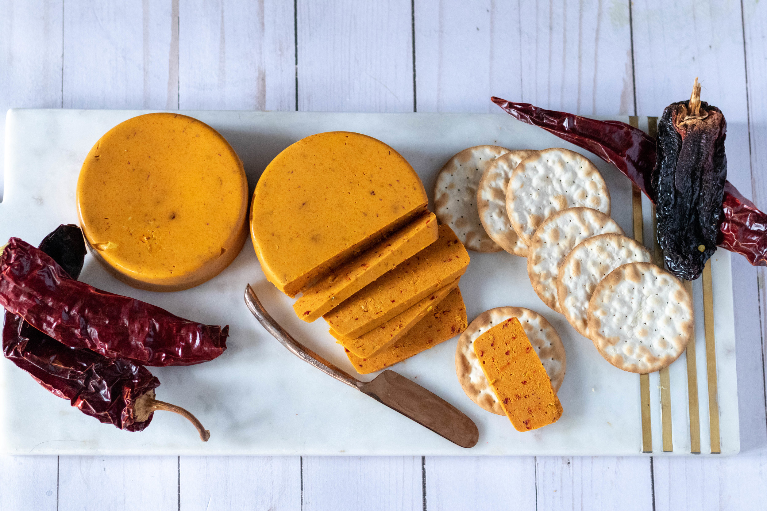 A cheese board with vegan coconut chile cheddar cheese surrounded by chiles and crackers