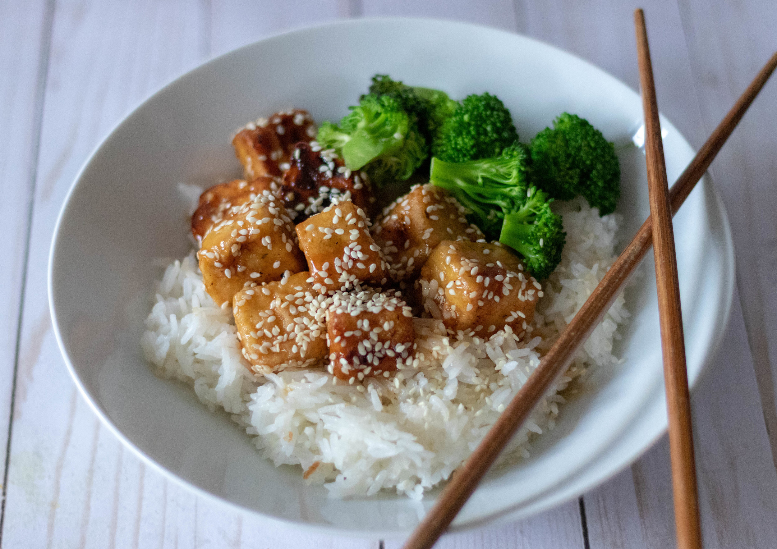 Sesame tofu over rice with broccoli.