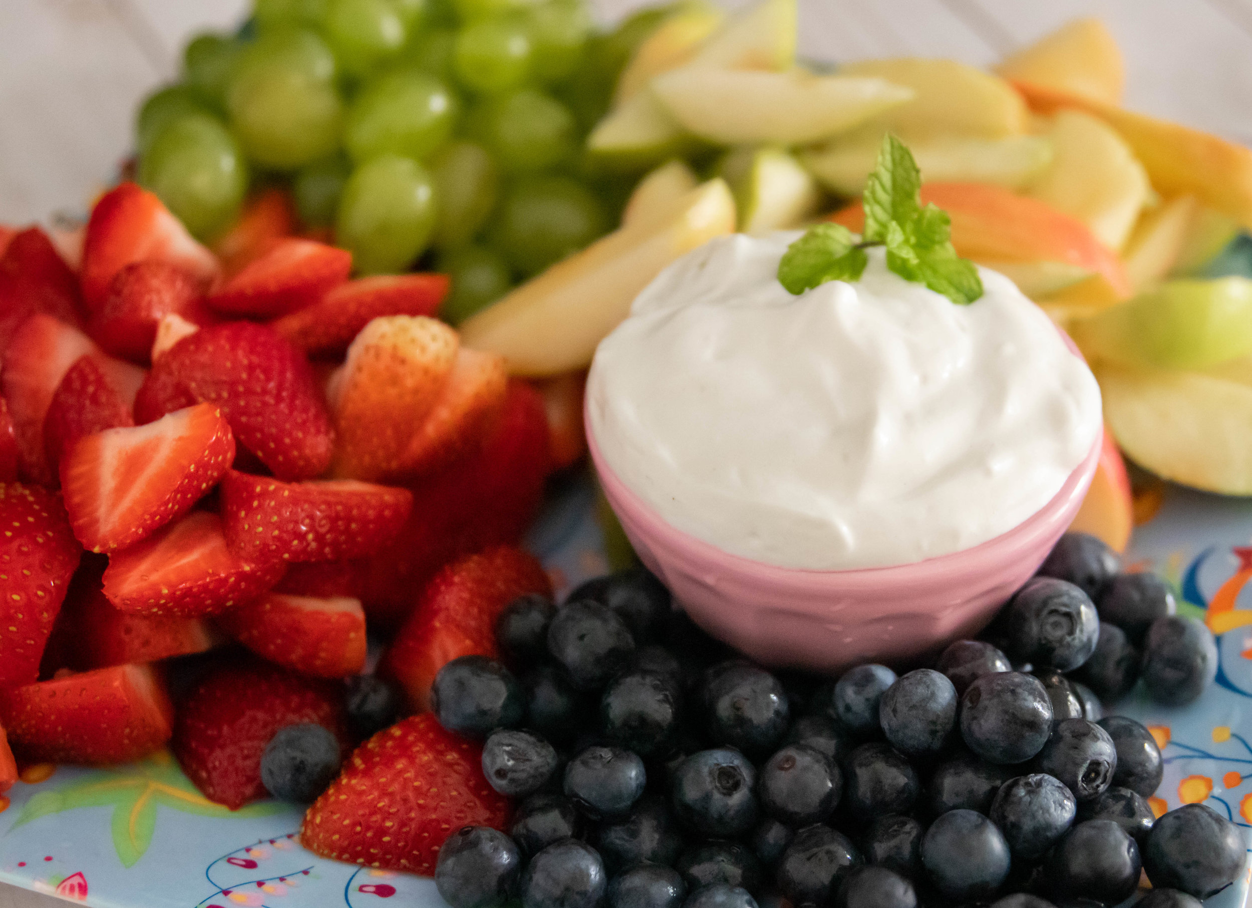Vegan marshmallow cream cheese fruit dip surrounded by strawberries, grapes, blueberries, and apples.