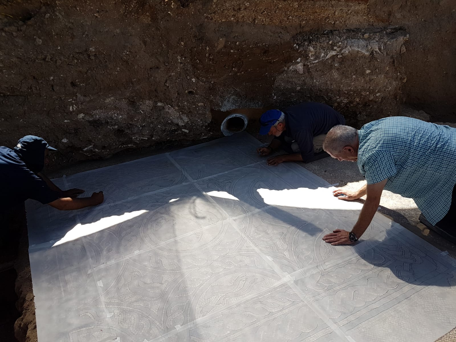 The conservation experts prepare to remove the mosaic for conservation. When the Visitors' Center is erected the mosaic will be displayed.  Photos: Raleb Abu Diab, IAA.