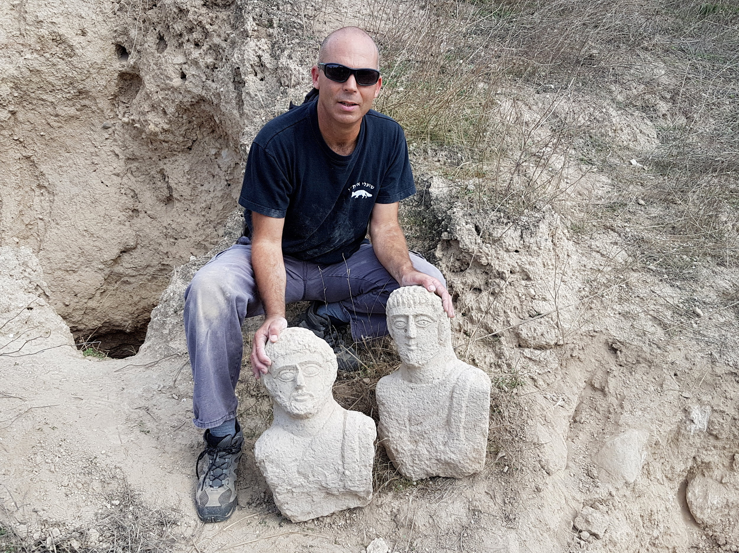 Nir Distelfeld, Israel Antiquities Authority Theft Prevention Unit inspector, with the two busts.  Photo: Eitan Klein, Israel Antiquities Authority