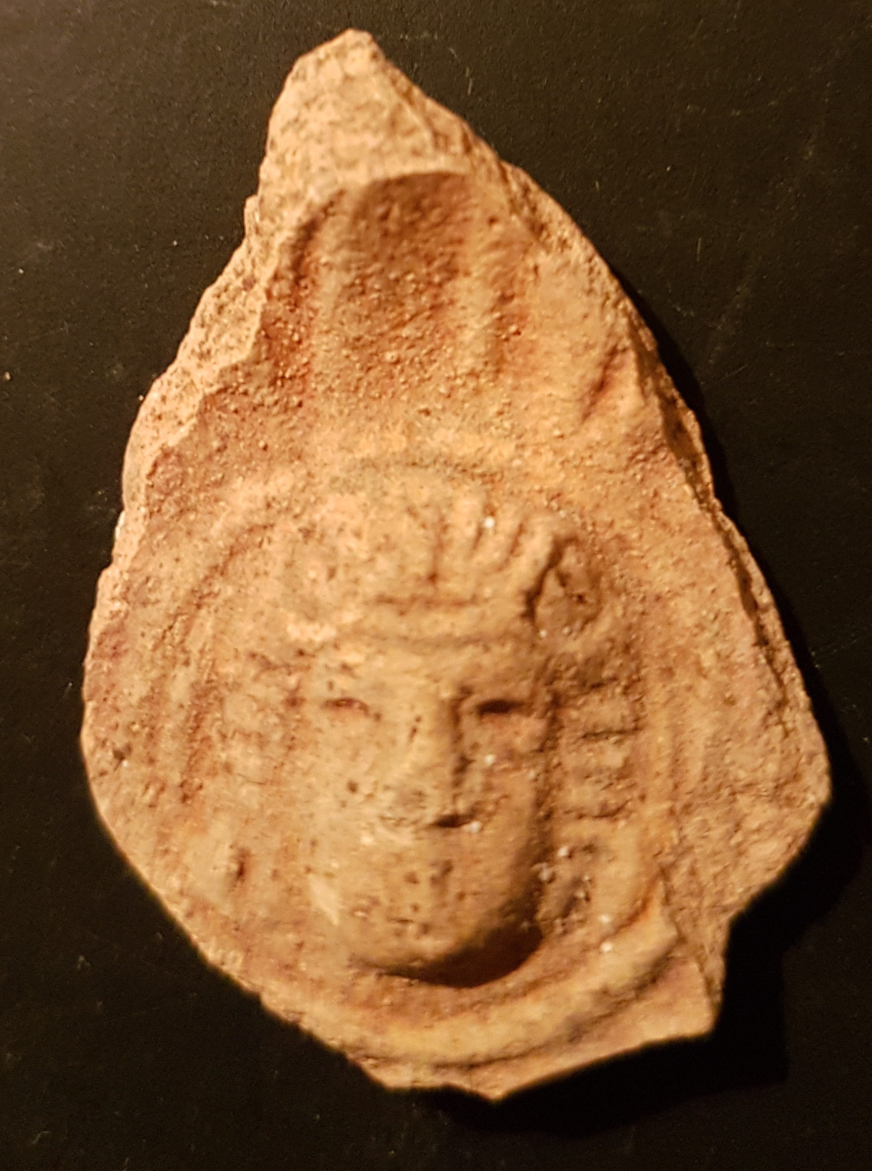 Molded face, possibly of a god, from a Roman oil lamp.  Photo: Tali Erickson-Gini, IAA