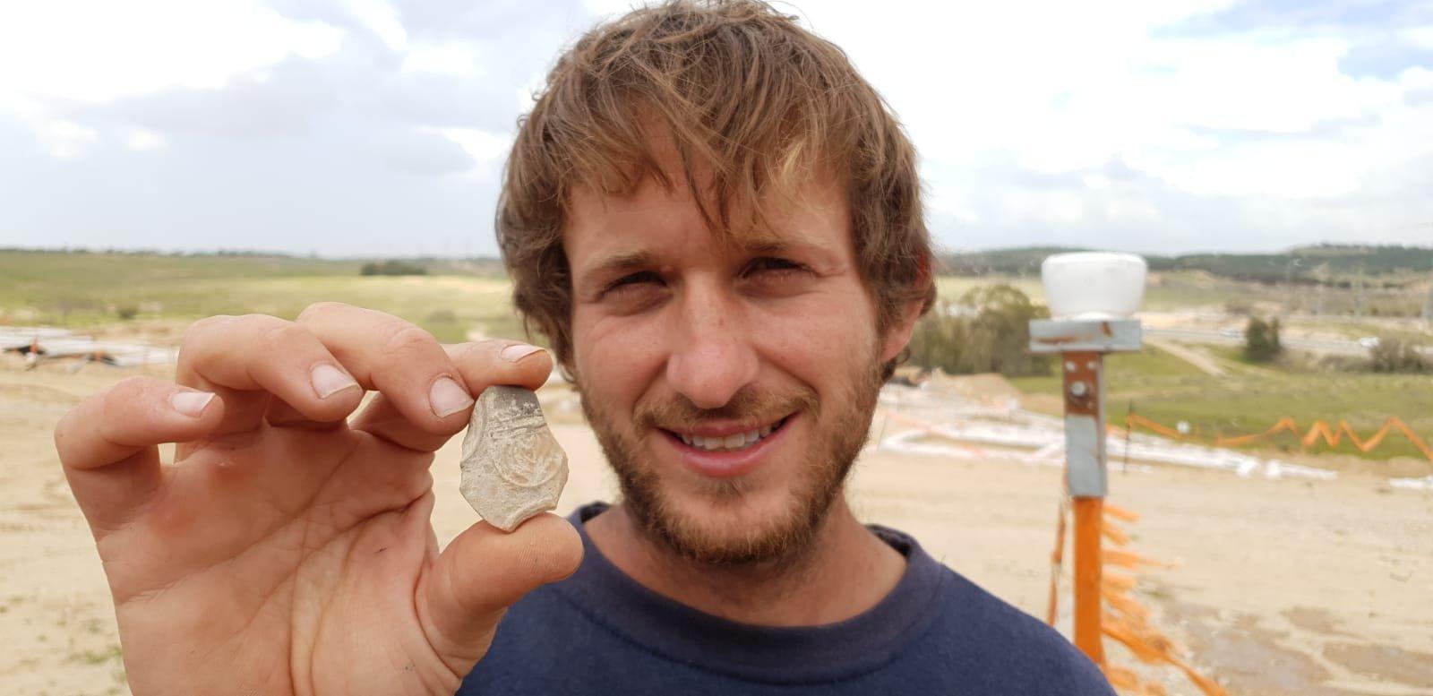 IAA Archaeologist Avinoam Lehavi holding the ancient Oil lamp sherd decorated with a menorah.