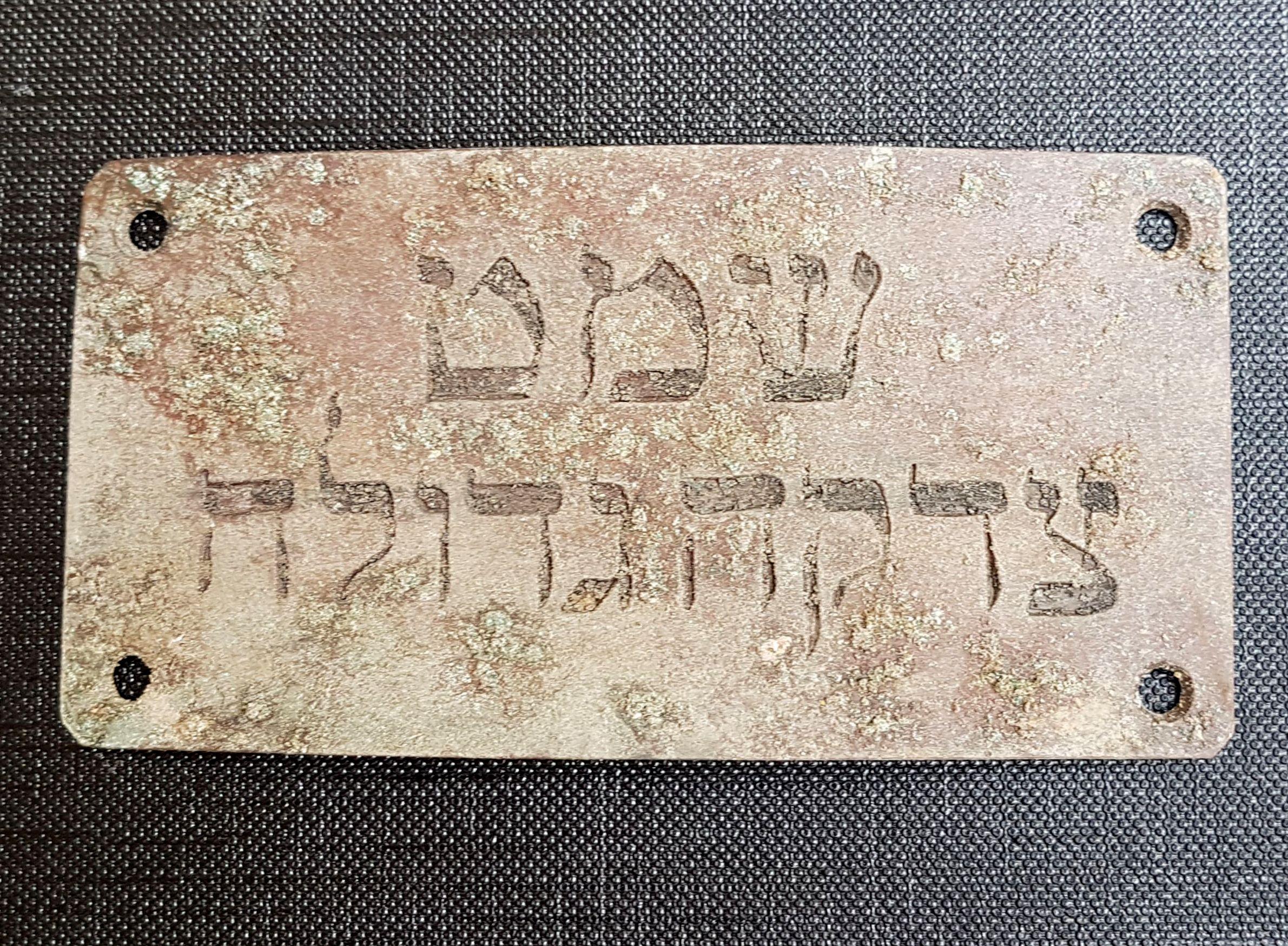 "The plaque of the director of the ""Tzedaka Gedola"" association.  Photo: John Seligman, Courtesy of the IAA"