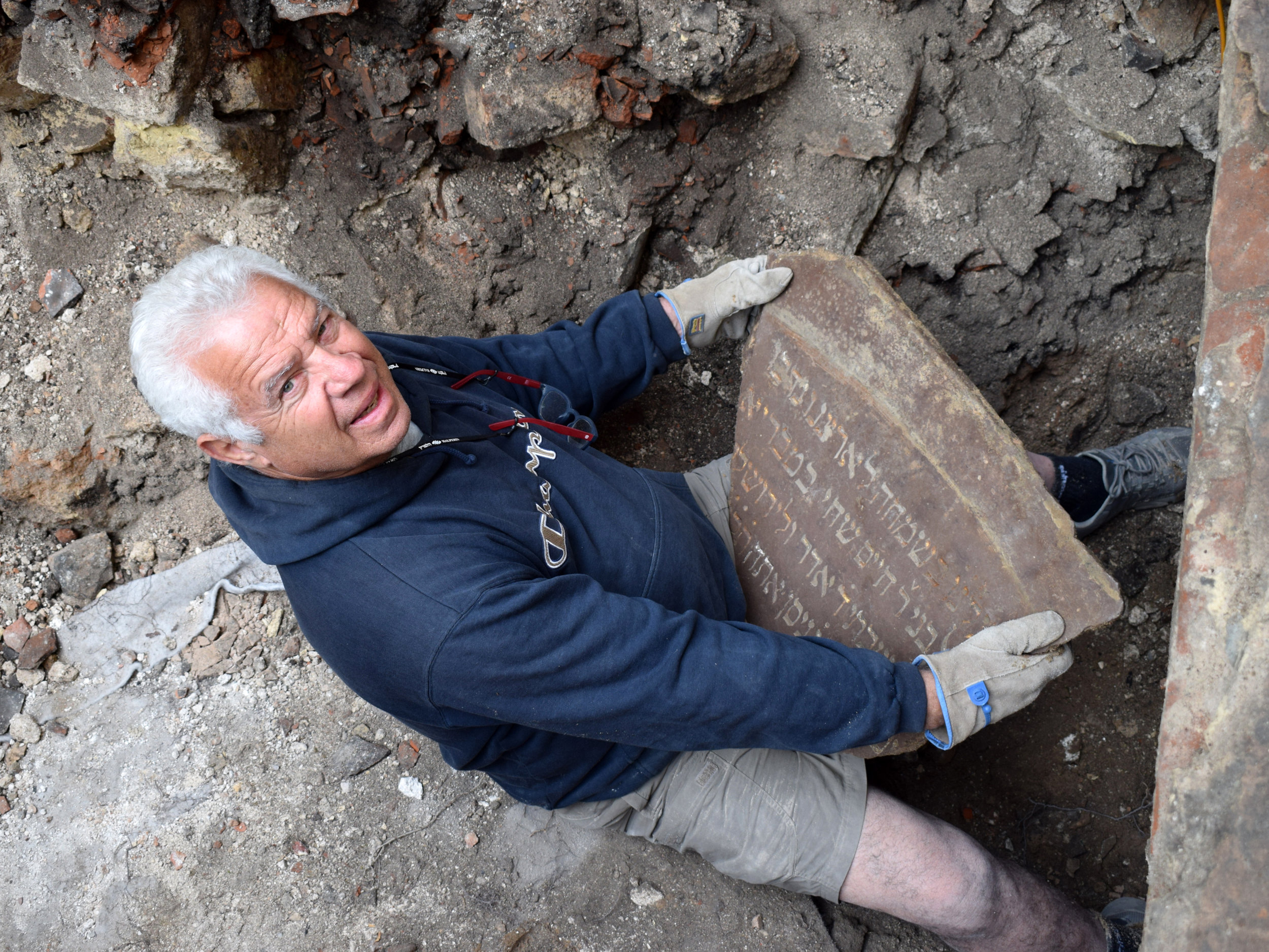 A member of the excavation team holding one of the inscription fragments.