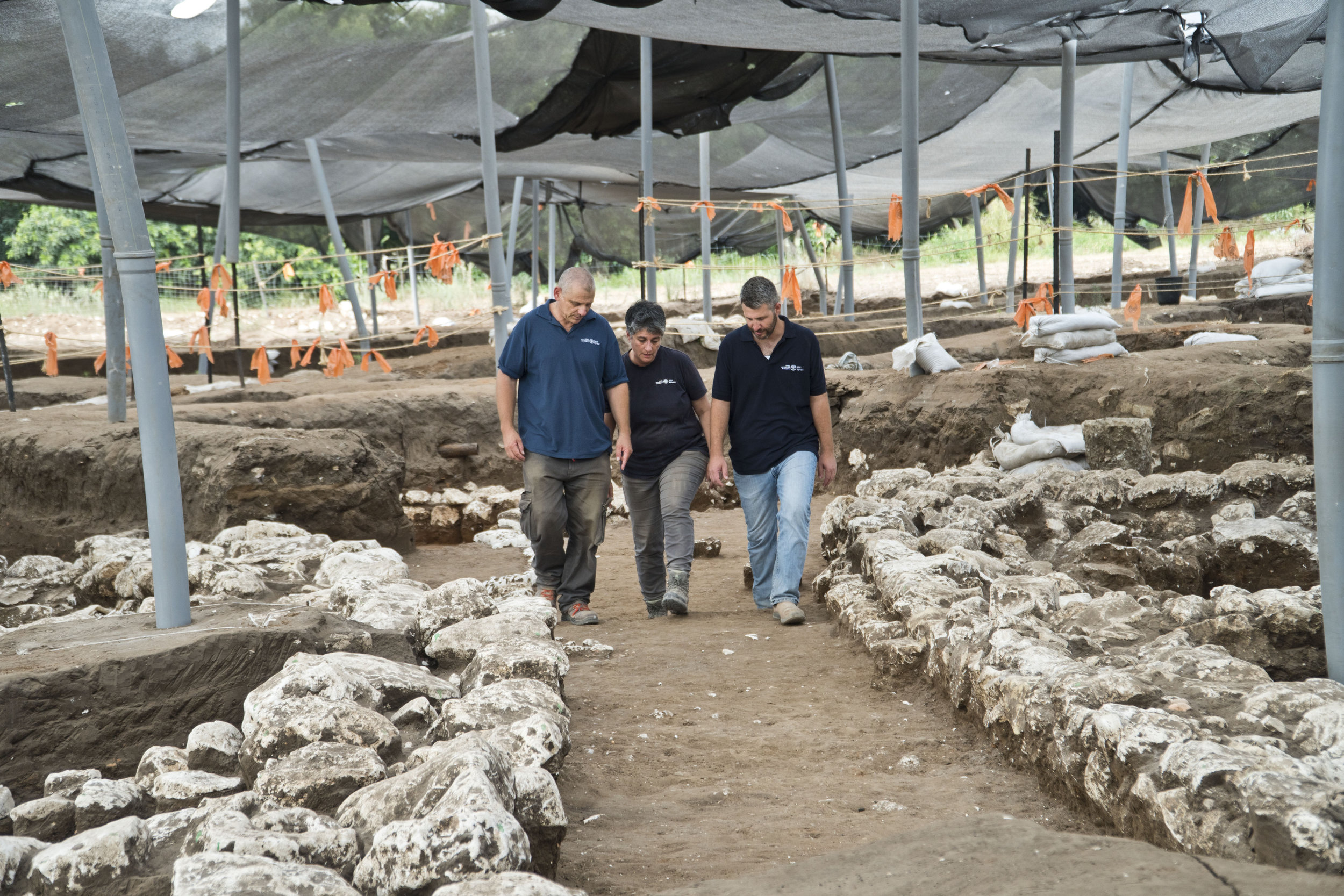 The excavation directors in a 5,000-year-old alley. Left to right: Dr. Yitzhak Paz, Dr. Dina Shalem, and Itai Elad.  Photo: Yoli Schwartz, Courtesy of the Israel Antiquities Authority
