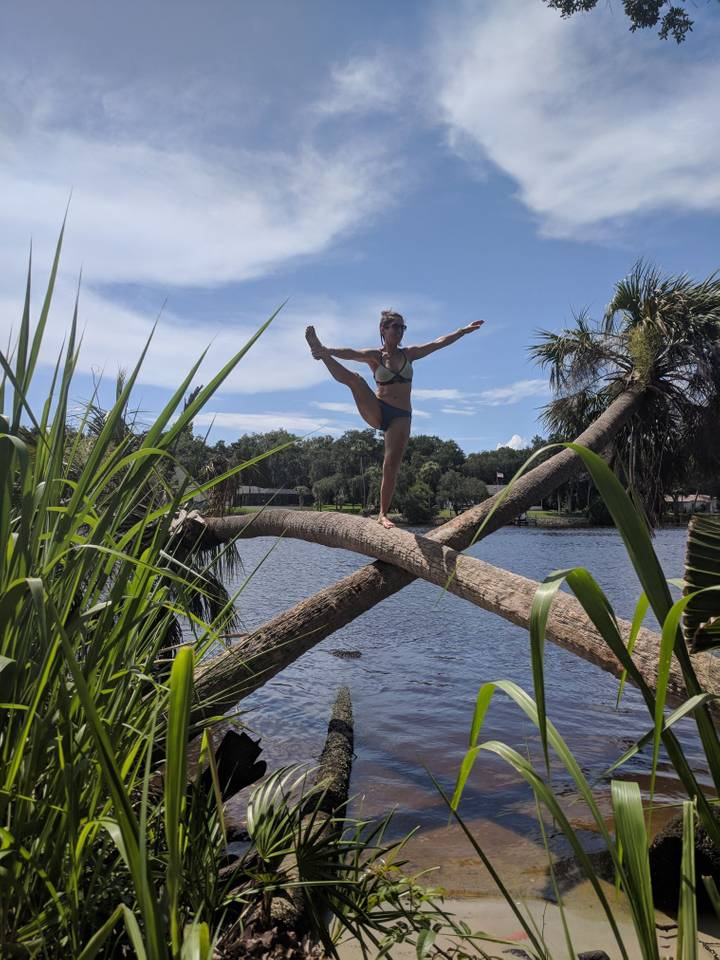 Young woman doing a stretching pose on two crossing palm trees