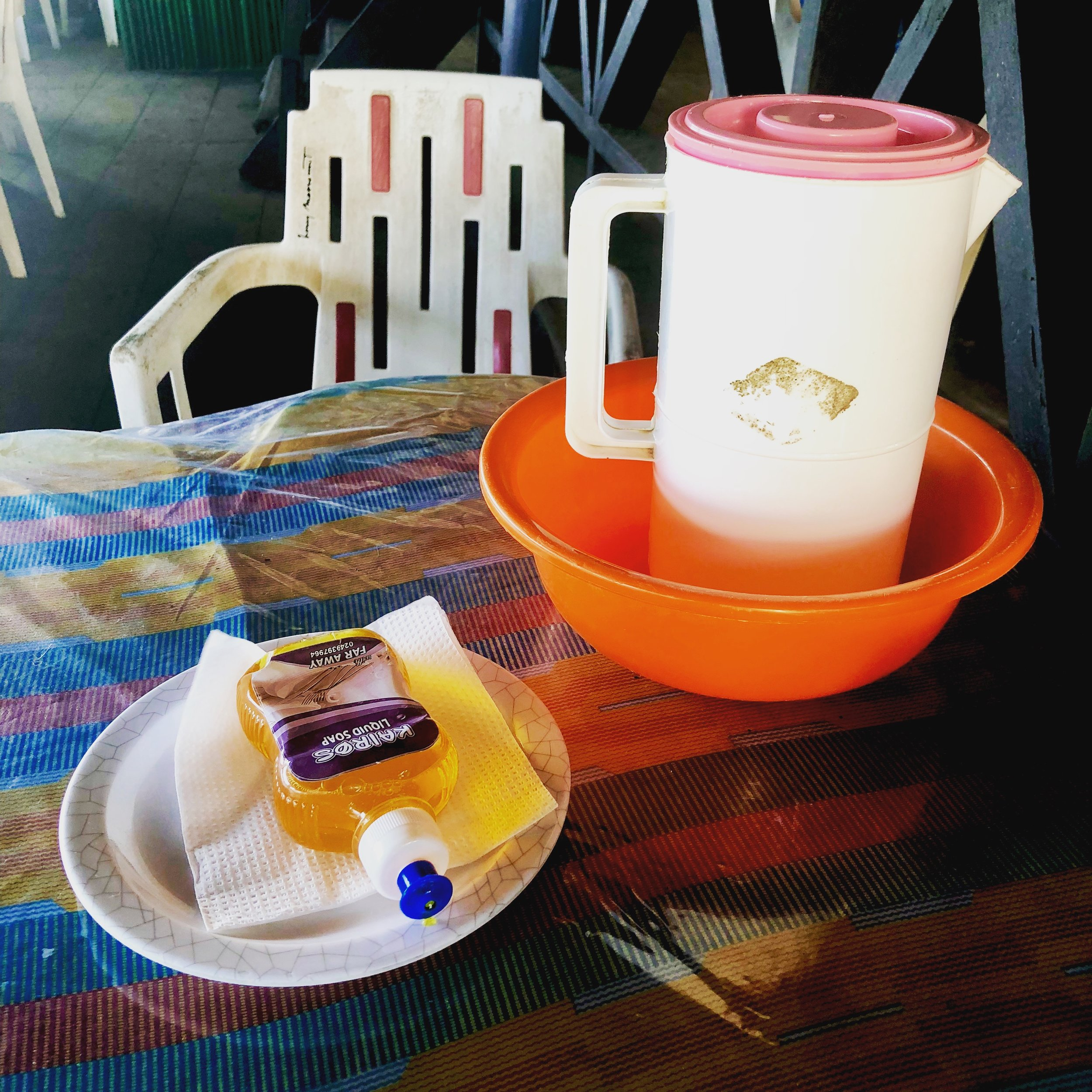 Typical hand washing supplies on restaurant tables in Ghana.