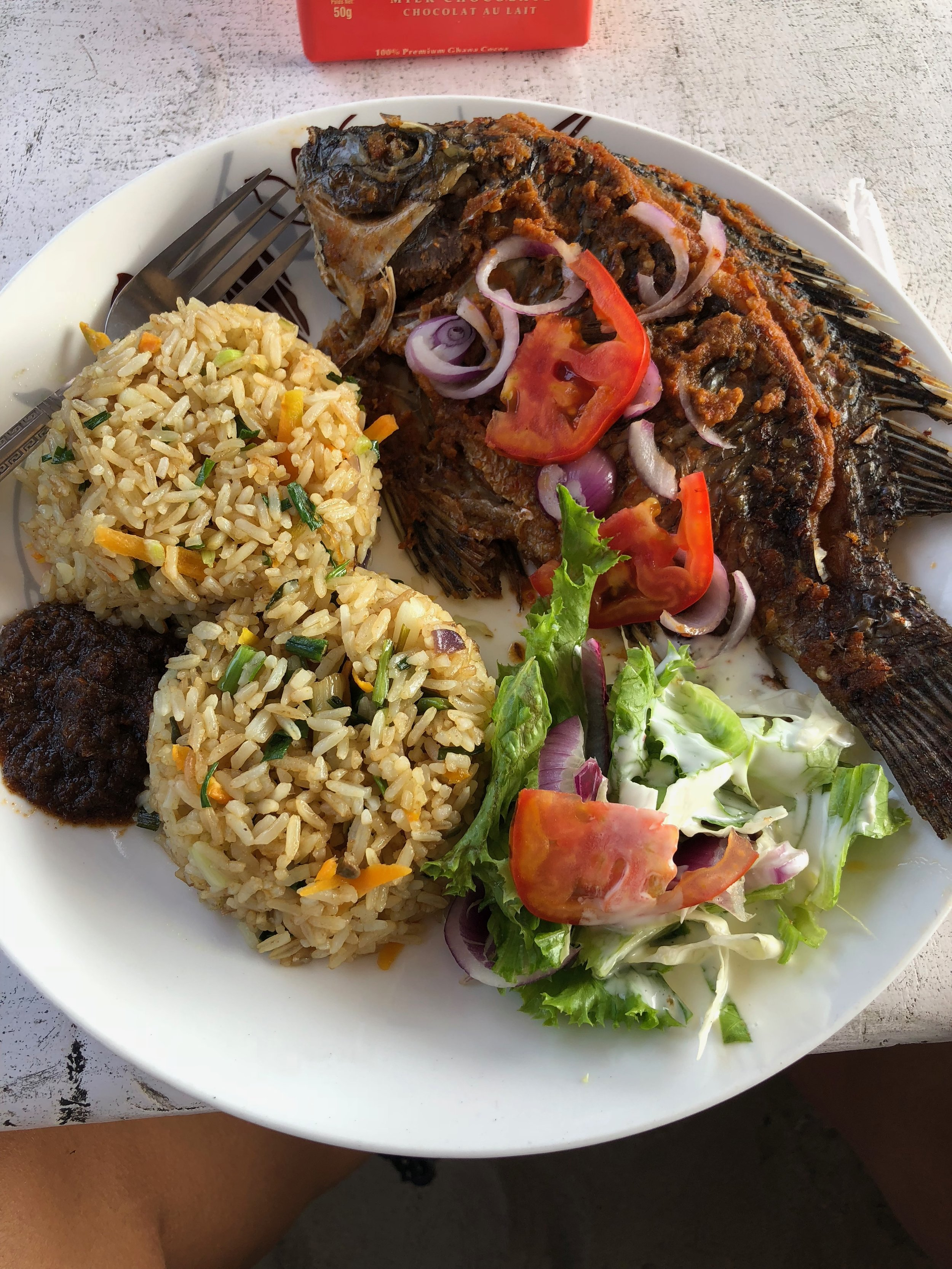 Typical Ghanaian meal with fish and jollof rice