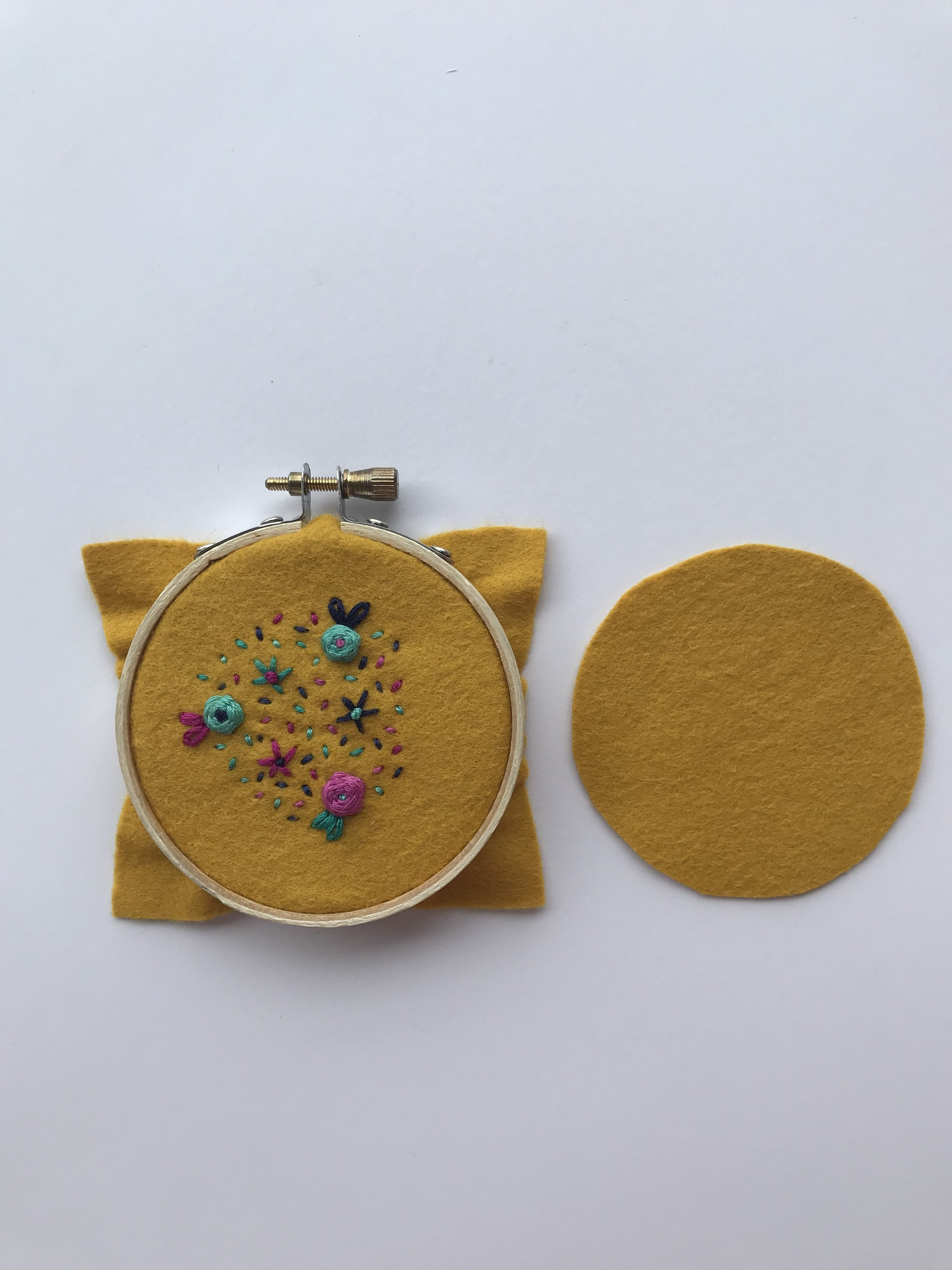 Once your design is complete, remove the embroidered piece of fabric from the hoop. Place the second piece of felt behind the embroidered felt.