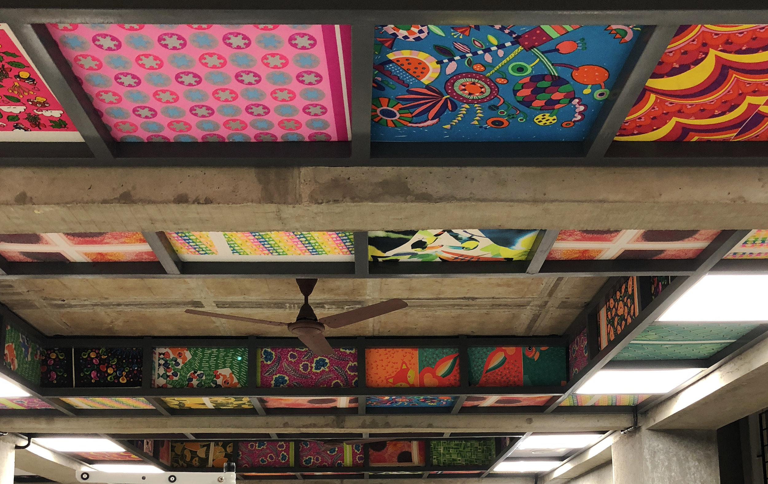 A patchwork of the colourful wraps we have created over the years adorn the ceiling.