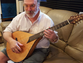 - Hi Ralph,Great to hear from you. The mandocello is just superb. Ray has shown immeasurable patience with me in setting it up to my picky/pesky specifications, and the instrument continues to grow richer as it's played in. It has such an amazing, rich tone, with excellent clarity and note separation. An absolutely luscious tone color and terrific response. I'm using a lot of superlatives here because I've played a lot of high-end acoustic instruments in the last 40-or-so years, and your five-course mandocello is right there at the top of the list. The skill that Ray put into the top just makes it sing--Sitka and mahogany is a marvelous, time-tested pairing, and the bear claw provides that extra stiffness to take what would have been a great top and push it toward spectacular. But it's not just the wood, it's Ray. He did some serious voodoo with the carving and the bracing of that top. And using a fixed bridge instead of the standard tailpiece really connects the instrument with itself. There's no wasted, reflected tone there; the inset bridge lets the notes germinate on themselves and affords a more organic, holistic sound--it's something that comes from within the instrument, not something that is thrust upon it by a clanky metal tailpiece. Ray Varona is a true top-tear craftsman, and that's not even getting into his visual aesthetic, which I could write a page about. In short, I couldn't be more pleased.Best,Jamie MillerYou can hear Jamie playing some of his compositions here:Stride,Field Of The LordCathedral