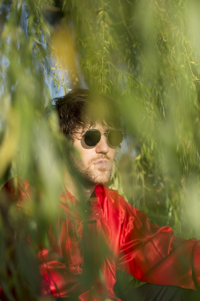 Bad Cop's Adam M. exhales amid the lush green foliage; photographed by Sam Saideman.