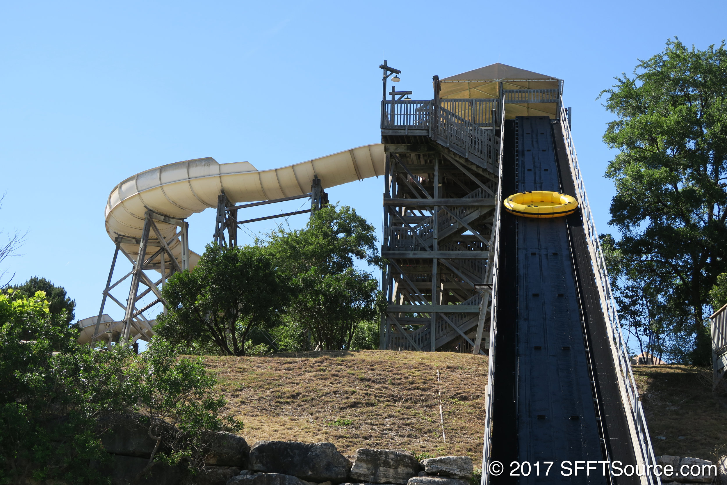 Rafts are transported to the top of the slide via conveyor belt.