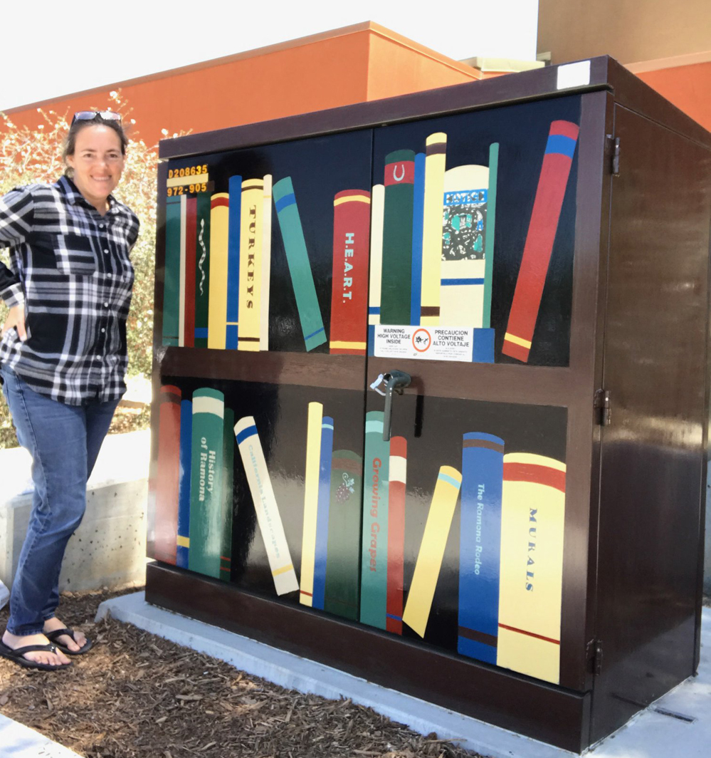 Artist Casey Buonaugurio turned a utility box on the 13th Street side of the Ramona Library into an eye-catching bookcase full of books. Photo Courtesy of the Ramona H.E.A.R.T.Mural Project