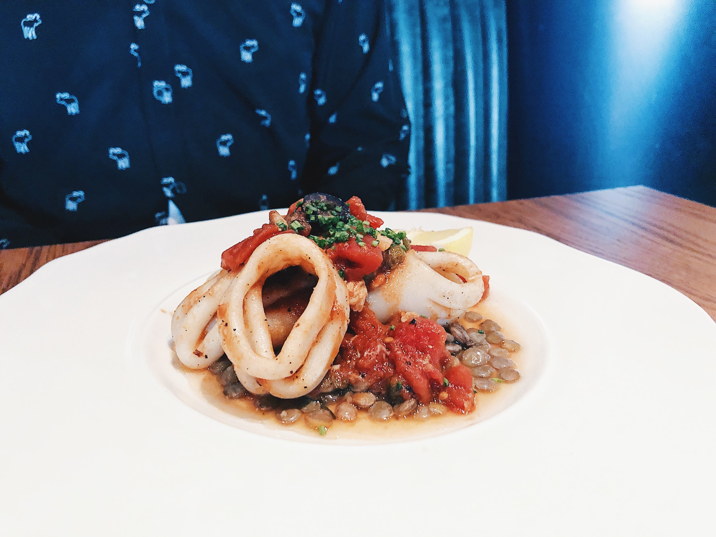 WOOD-GRILLED SQUID  - puttanesca-style, capers, lemon, tomato, olives, anchovy sauce, braised Cumbrian lentils, grilled lemon