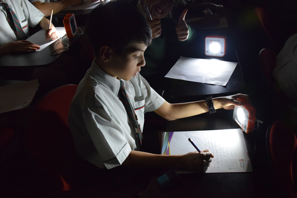 A student at St Michaels School writing his letter to his new SolarBuddy, whilst using the amazing light!