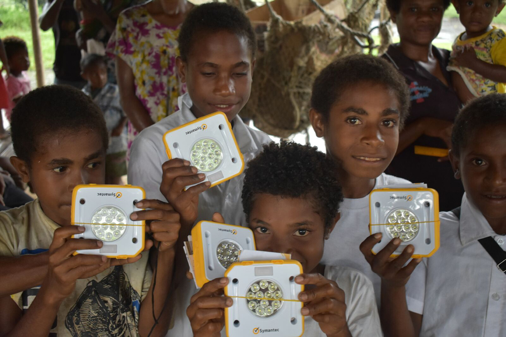 Students in PNG receiving their SolarBuddy lights, kindly donated by Symantec. Symantec took part in a worldwide work place giving event and all of their lights were distributed to children living in energy poverty, in PNG.