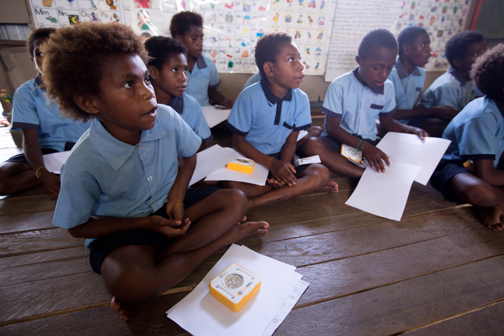 Students in PNG being taught how the SolarBuddy lights work and how to take care of them.