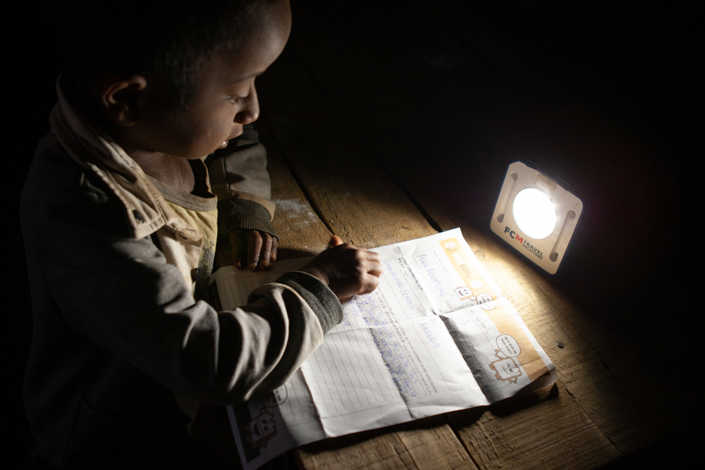 A student in Madagascar using his SolarBuddy lights for the first time in the dark.