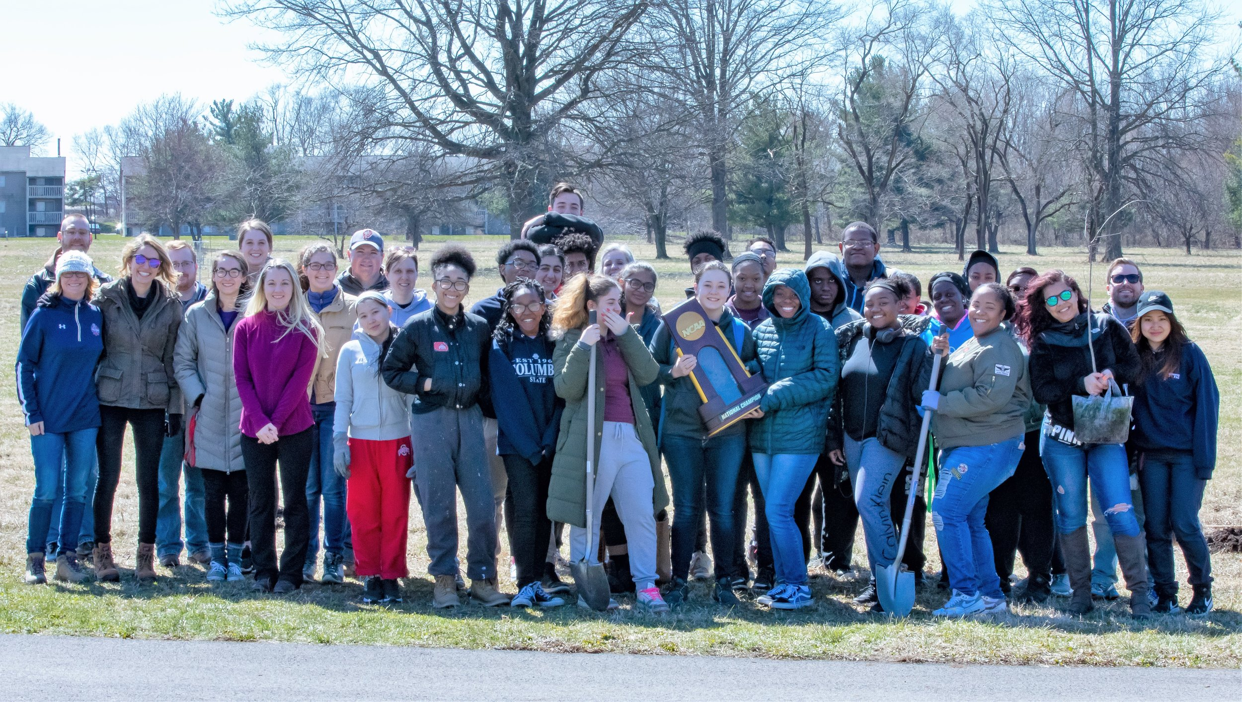 community volunteers pose with the NCAA Women's Final Four trophy after a morning of planting trees at Walnut Hill Park. April 23, 2018. Photo: CLOC