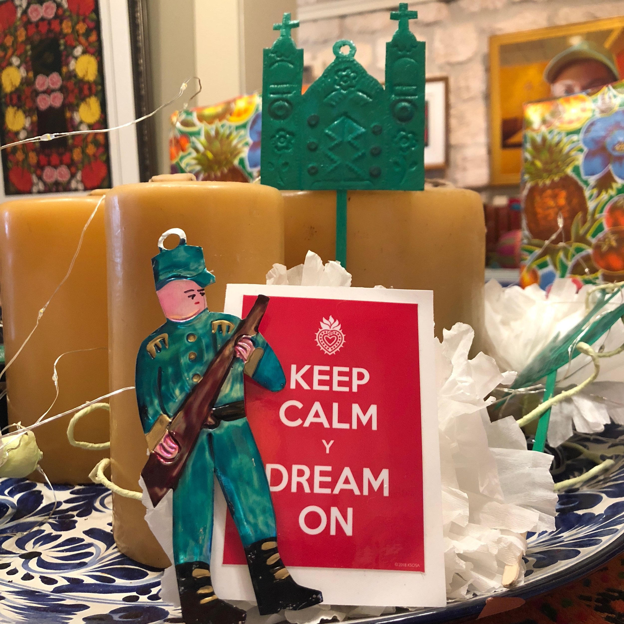 "SosaGalleries SouthTown San Antonio, Texas March 7, 2018 Photo by KSosa  ""I took this photo in our art gallery which is full of Mexican inspired art and objects. I used the Mexican tin ornaments of the Cathedral to symbolize sanctuary and the little man with the gun is probably a 'federale' but he is doing double duty here as a border patrol agent."" - Kathy Sosa"