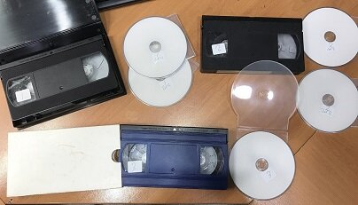 3 vhs tapes with copies of dvd's next to them on a table, video tapes copied to DVD with labels