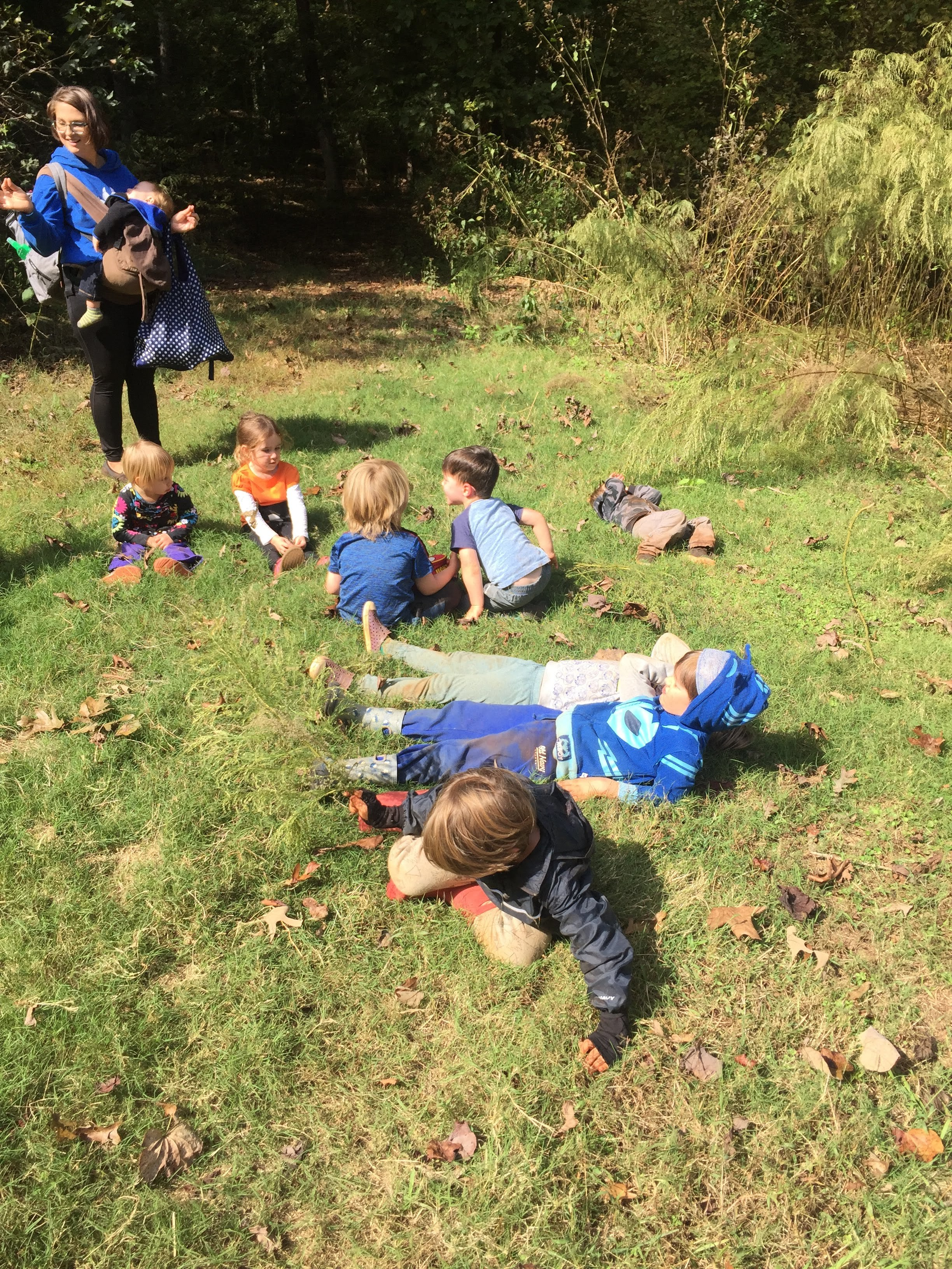 """A beautiful impromptu moment with the children """"charging their batteries"""" in the sun. As we left the shady cool forest and found the meadow bathed in sunlight, they all spontaneously dropped to the ground and lolled, took yoga poses, rolled, and sprawled in the warmth."""