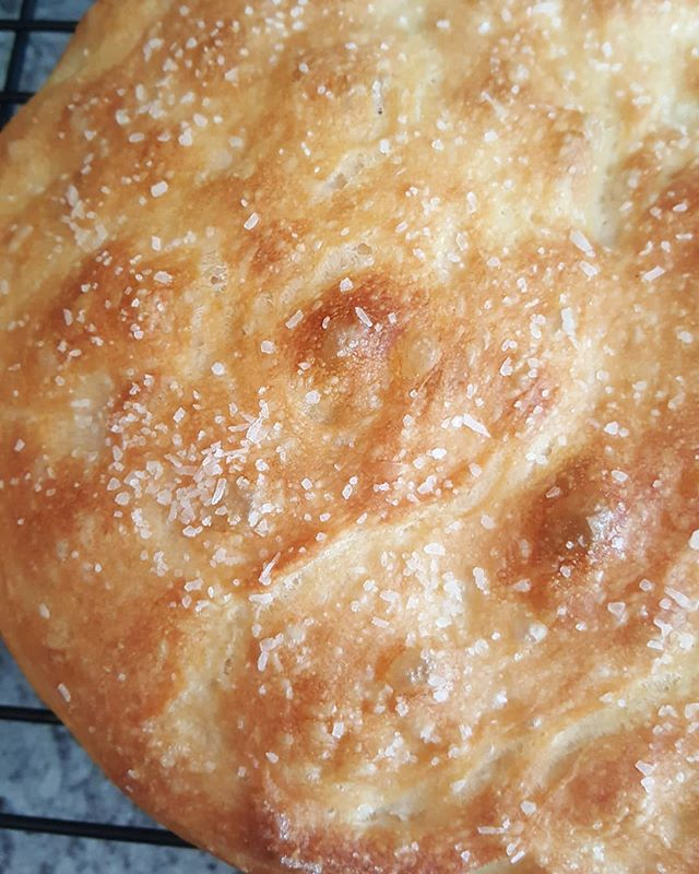 Fresh hot focaccia bread straight out of the oven. 1 sea salt and 1 rosemary.