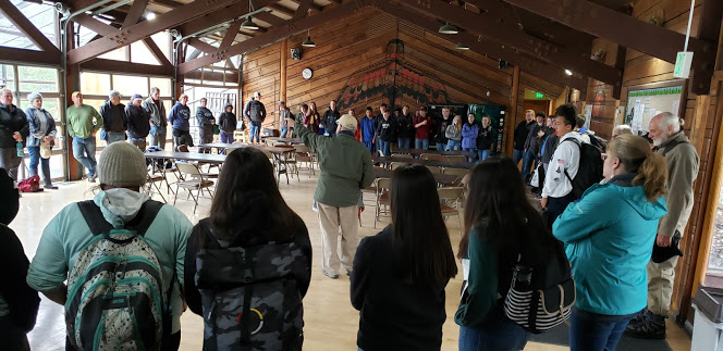 Swinomish elder, Raymond Mitchell, welcomes and educates La Conner grade 8 students on the historic significance of their research site, Lone Tree Point before heading to the beach.