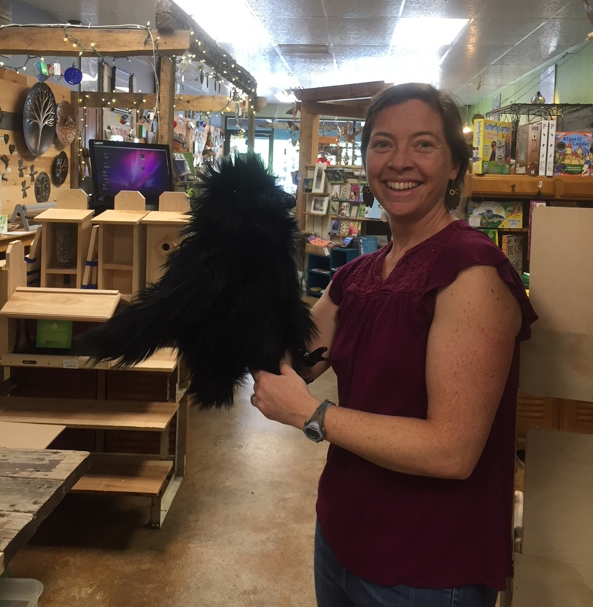 Kendra playing with a raven puppet in Raven Tree Shop in mount shasta