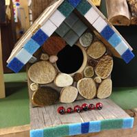 T his birdhouse is Mosaiced with tiles and stones.