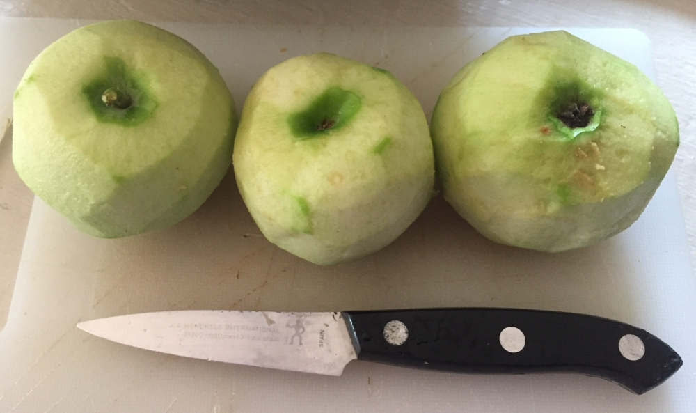 Peeled green apples are ready to slice for pies.