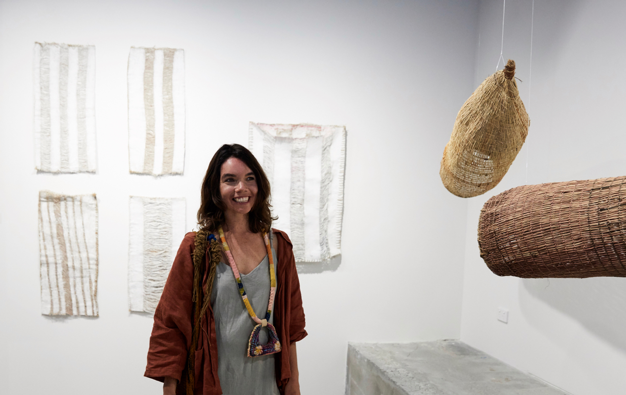 Freja Carmichael with artworks (left) Nadeena Dixon,  Spirit Lines  series and (right) Bonnie Burangarra,  Fish Traps . Photography by Flashpoint Labs.
